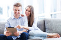 Young couple looking at digital tablet on sofa with Royalty Free Stock Image