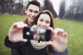 Young couple looking happy taking self portrait while pictures using a smart phone at the park teenage boy and girl in love Royalty Free Stock Photo