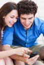 Young couple looking at mobile phone people with smiling Royalty Free Stock Image