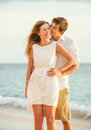 Young couple in love on the beach sunset attractive men and women enjoying romantic date at Stock Photos
