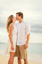 Young couple in love on the beach sunset attractive men and women enjoying romantic evening at Royalty Free Stock Image