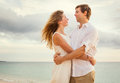 Young couple in love on the beach sunset attractive men and women enjoying romantic evening at Royalty Free Stock Photography