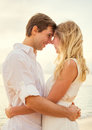 Young couple in love on the beach sunset attractive men and women enjoying romantic evening at Royalty Free Stock Photos