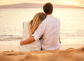 Young couple in love on the beach sunset attractive men and women enjoying romantic evening watching Stock Image