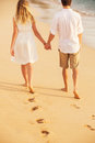 Young couple in love on the beach sunset attractive men and women enjoying romantic walk at holding hands Stock Images