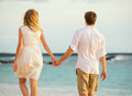 Young couple in love on the beach sunset attractive men and women enjoying romantic walk at holding hands Stock Photo