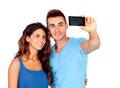 Young couple in love by becoming a photo with mobile isolated on white background Stock Photos