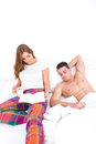 Young couple in love relaxing in bed girl reading book wih coffee while men is sleeping next to her Stock Photo