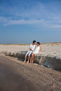 Young couple in love sitting on the beach Stock Images