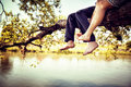 Young couple in love sitting cross-legged on a tree branch above the river in nice sunny day. Photo is colorized in warm tints Royalty Free Stock Photo