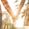 Young couple in love walking the autumn park holding hands looking the sunset Royalty Free Stock Photos