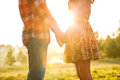 Young couple in love walking the autumn park holding hands looking the sunset Royalty Free Stock Images
