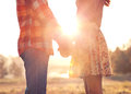 Young couple in love walking the autumn park holding hands looking the sunset Royalty Free Stock Photo