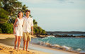 Young couple in love walking on the beach at sunset attractive men and women enjoying romantic evening walk watching Stock Photo