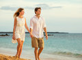 Young couple in love walking on the beach at sunset attractive men and women enjoying romantic evening walk watching Royalty Free Stock Image