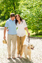 Young couple in love walking dog park Stock Photo