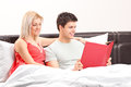 A young couple lying on a bed and reading a book Royalty Free Stock Image