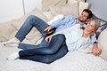 Young Couple lying On A Couch and watching TV Royalty Free Stock Photos