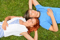 Young couple lying on grass eyes closed enjoy summertime top view Royalty Free Stock Photos