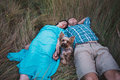 Young couple lying on the grass holding hands and small dog between them Royalty Free Stock Photo