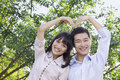 Young couple making a heart shape with their arms Royalty Free Stock Photo
