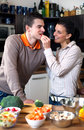 Young couple making and tasting salad Royalty Free Stock Images
