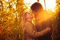 Young couple man and woman hugging and kissing in love romantic outdoor with sun light autumn nature on background fashion trendy Stock Photos