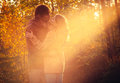 Young couple man and woman hugging and kissing in love romantic outdoor with sun light autumn nature on background fashion trendy Royalty Free Stock Photo
