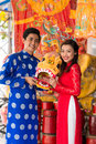 Young couple with a mask of lion in ao dai dresses holding Stock Photos