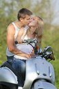 Young couple on motorbike / scooter on nature Royalty Free Stock Photography