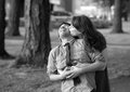 Young couple necking in the park monochrome toned image of a romantic laughing and kissing Stock Photo