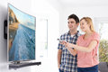 Young Couple With New Curved Screen Television At Home Royalty Free Stock Photo