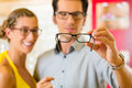 Young couple at optician with glasses Stock Images