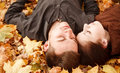 Young couple outdoors lying down on autumn leaves eyes closed Royalty Free Stock Images