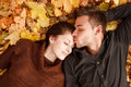 Young couple outdoors lying down on autumn leaves eyes closed he kissing her Royalty Free Stock Photo