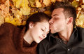 Young couple outdoors lying down on autumn leaves eyes closed he kissing her Stock Images