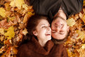 Young couple outdoors lying down on autumn leaves laughing having good time Royalty Free Stock Image