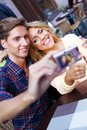 Young couple outdoors taking picture of themselves in summer cafe Royalty Free Stock Photo
