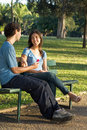 Young Couple on a Park Bench -- Vertical Stock Photo