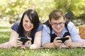 Young Couple at Park Texting Together Royalty Free Stock Photos