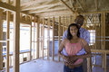 Young couple in partially built house, man embracing woman, smiling, portrait Royalty Free Stock Photo