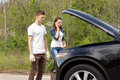 Young couple phoning for roadside assistance Royalty Free Stock Photo