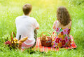 Young couple at picnic with kitten in a basket a sitting back to camera Stock Photography