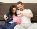 Young couple with piggybank at home cheerful putting banknote in Stock Image