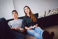 Young couple playing video games indoors together while sitting in their living room mixed race teenage holding game console Royalty Free Stock Photos