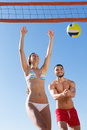 Young couple playing volleyball at sea beach Stock Images