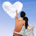 Young couple pointing at heart clouds shaped of on the sky Stock Photography