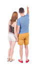 Young couple pointing in shorts and t shirt back view rear view people collection backside view of person isolated over white Stock Images
