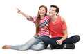 Young couple pointing sitting over white background Stock Photo