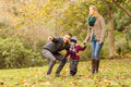 Young couple pointing something to their little boy on an autumns day Royalty Free Stock Photo